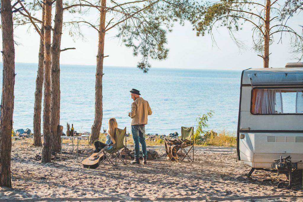 Un couple profite de la nature en camping avec leur van aménagé.