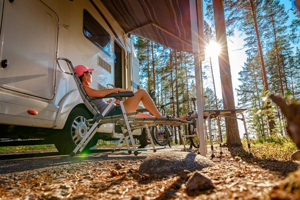 Une femme se repose devant un van aménagé