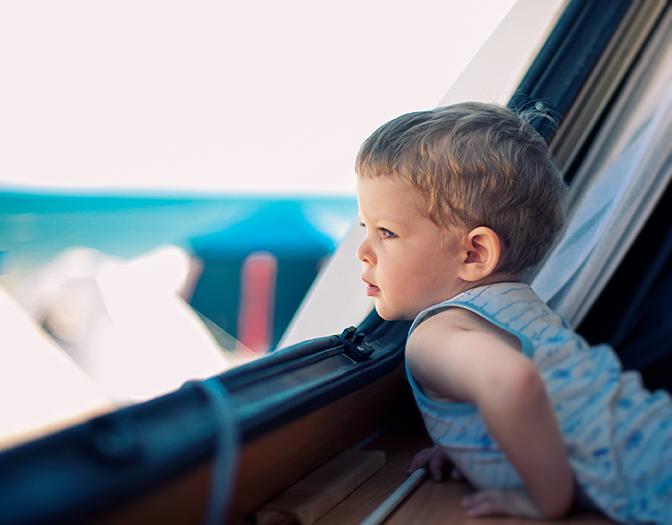 Un jeune enfant regarde par la fenêtre du van aménagé.