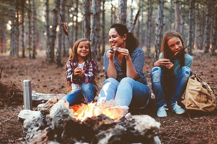 Une famille assise près du feu de camp fait griller des saucisses