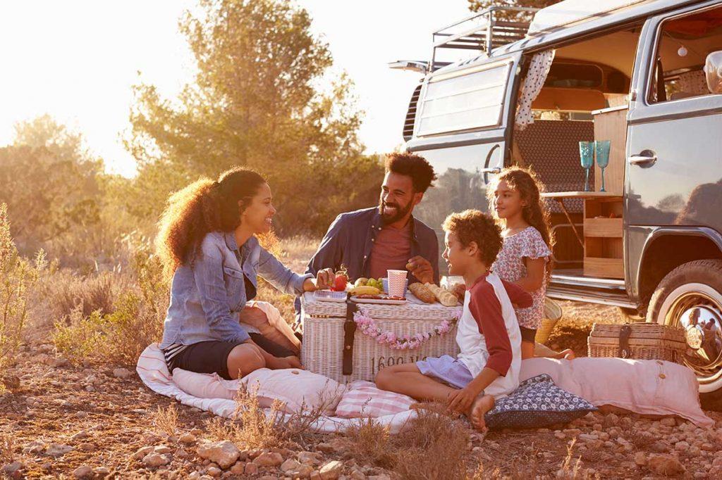Une famille fait un pique-nique devant leur van aménagé.