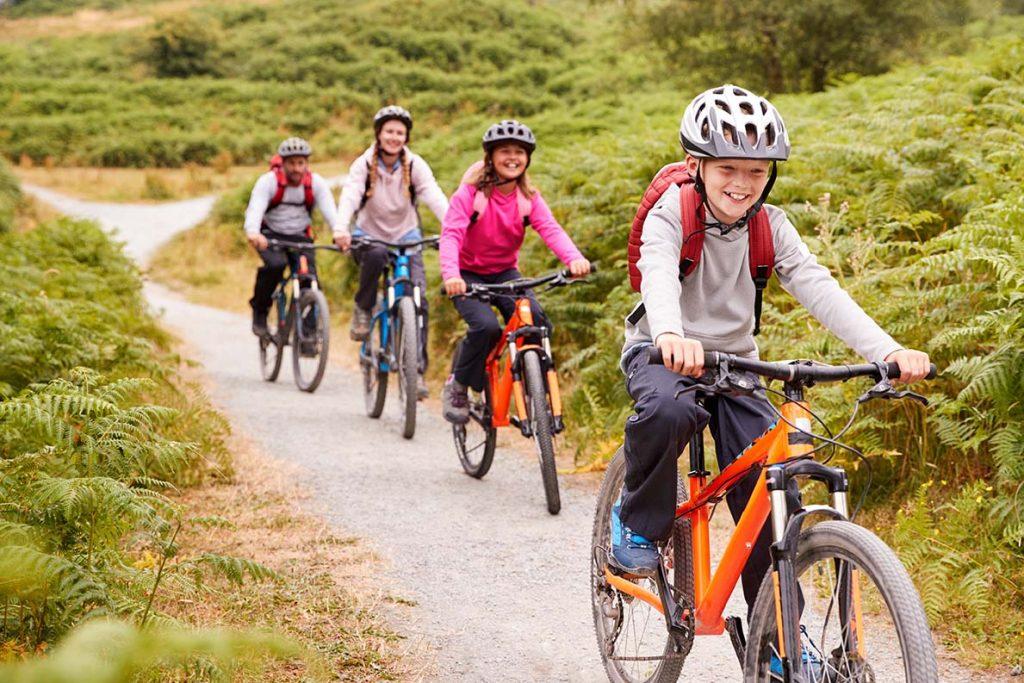 Une famille fait une ballade à vélo sur une piste cyclable en nature.