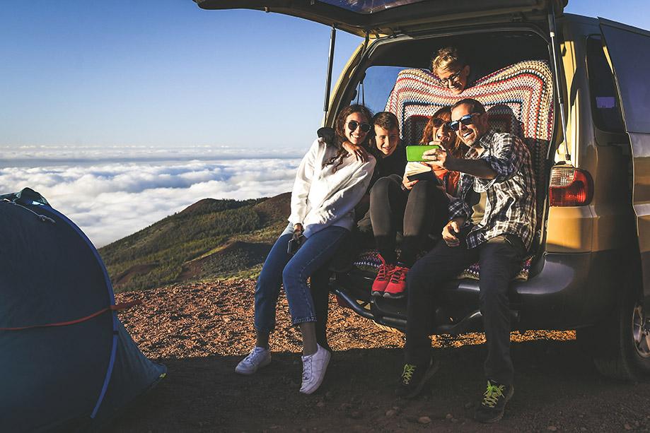 Un groupe d'amis posent pour un selfie à l'arrière de leur van.