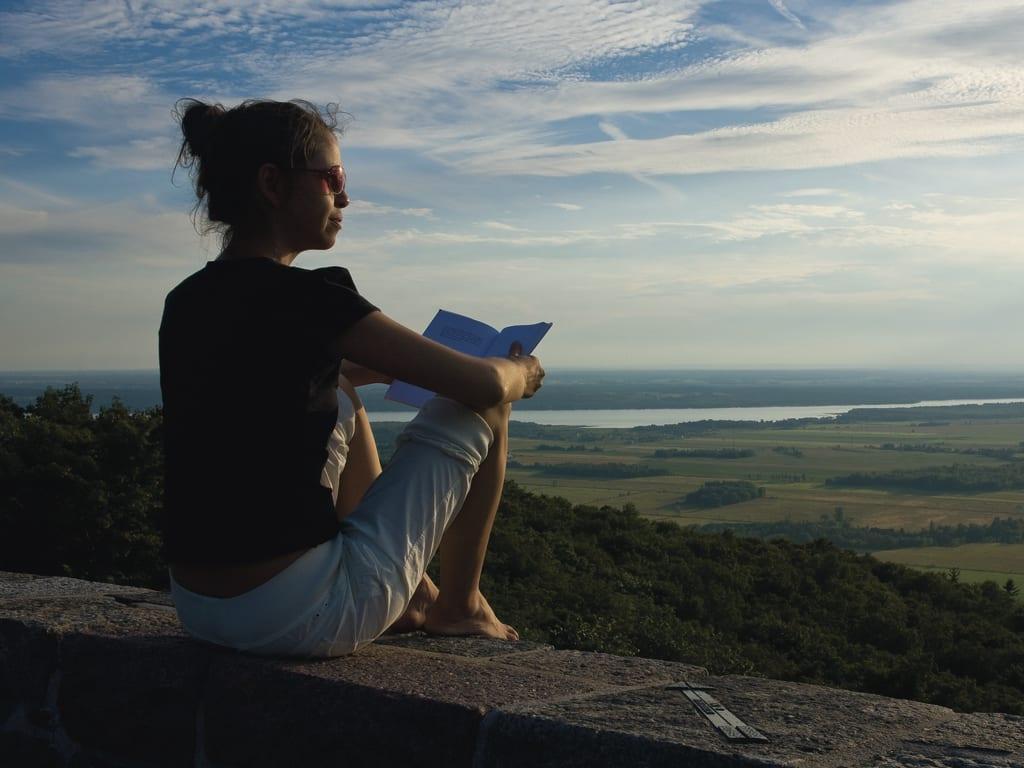 Une femme relaxe en lisant un livre devant un magnifique paysage québecois